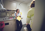 Young female internal medicine resident physician speaking with seated middle age female patient in examination room