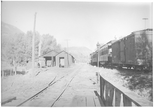 West-facing view of RGS West Durango terminal as seen from the deck of Bridge 162-A showing the engine house and bus barn with locomotive activity.  A mixed train is waiting on the north siding.<br /> RGS  West Durango, CO  Taken by Barriger, John W. III - 7/3/1938