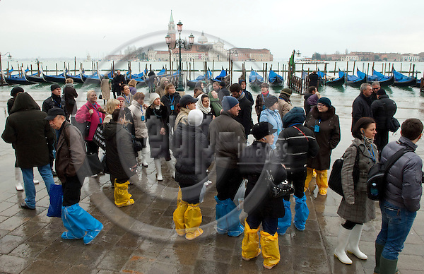 San Marco-Venice-Italy - December 24, 2010 -- Acqua alta, high tides, floods, gondolas tied up and a group of tourists ready for a wet excursion -- water, infrastructure, tourism, people -- Photo: Horst Wagner / eup-images