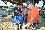 Robel Haile, a 13-year old resettled refugee from Ethiopia, feeds animals on a farm in Linville, Virginia, on July 17, 2017, with help from Holly Mumaw, who volunteers to help Haile and other refugee youth, resettled in the area by Church World Service, prepare to show sheep and goats in a county fair.<br /> <br /> Photo by Paul Jeffrey for Church World Service.