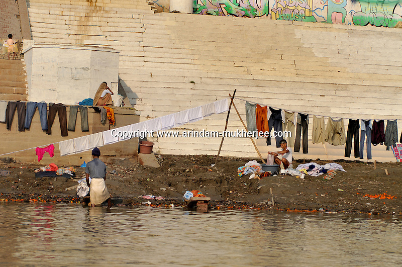 Indian laundrey men washing clothes in a ghat in Varanasi, Uttar Pradesh, India.