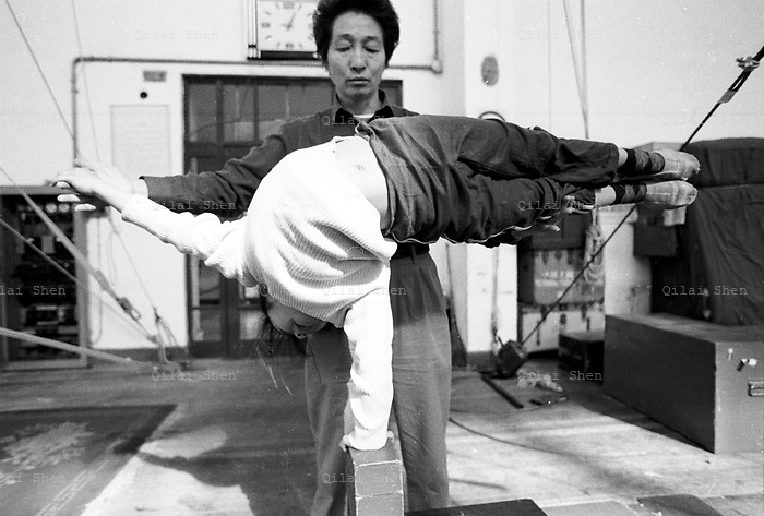 QSFeature01Acrobats022 20010414 SHANGHAI, CHINA: A coach adjusts the posture of a young student at the Shanghai Circus School in Shanghai, China 14 April 2001. Traditional entertaiment such as acrobatic shows are loosing audiences and popularity in China, and the students will likely face a tough time when they finally finish six years of grueling training..Photo by: Qilai Shen