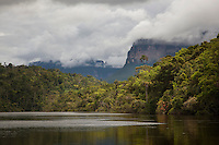 Tepuis, large flat topped mountains, stand all along the winding Canaima River, in Canaima National Park, Venezuela. Auyantepui seen here is home to Angel Falls, the tallest single drop waterfall in the world