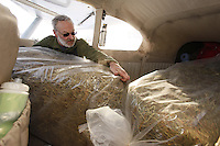 February 16, 2013  Volunteer Iditarod Air Force pilot Greg Miller loads his Cessan with Hay and musher food bags at the Willow airport as musher food, straw, HEET and people food is flown to the 4 checkpoints on the east side the Alaska Range. ..Iditarod 2013 Photo Copyright Jeff Schultz  -- Do not reproduce without written permission