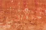 A Fremont style petroglyph panel, carved in Classic Vernal style over an older, faded Barrier Canyon style pictograph panel with dark, ghost-like figures.  Sego Canyon, Utah.