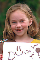 Girl age 8 holding we love you sign in Grand Old Day parade.  St Paul  Minnesota USA