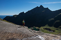 Female hiker takes in view of mountain peak rising above Djupfjord, Moskenesøy, Lofoten Islands, Norway