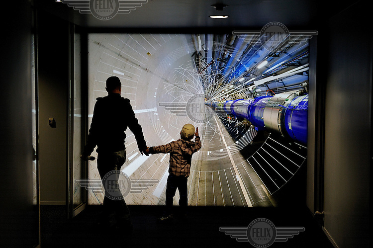 A man and child are silhouetted against an enhanced photographic image at the entrance to CERN's control centre showing the 27 kilometre long Large Hadron Collider (LHC), the world's largest and most powerful particle accelerator. It was used to confirm the apparent existence of the Higgs Boson or Higgs particle. CERN (originally: Conseil Europeen pour la Recherche Nucleaire, now the European Organization for Nuclear Research) was established by 12 Western European countries in 1954. In October 2013 the Nobel prize in physics was awarded to CERN's Francois Englert and Peter Higgs for their theoretical work on the Higgs boson