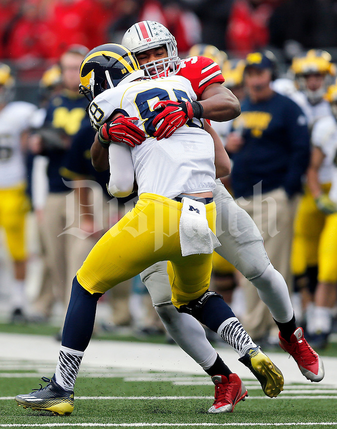 Ohio State Buckeyes linebacker Joshua Perry (37) tackles Michigan Wolverines tight end Jake Butt (88) during the fourth quarter of the NCAA football game against Michigan at Ohio Stadium on Saturday, November 29, 2014. (Columbus Dispatch photo by Jonathan Quilter)