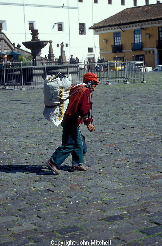 Iindian man carrying a heavy load on his back in the Old Town, Quito, Ecuador. Old Quito was made a UNESCO World Heritage Site in 1978.