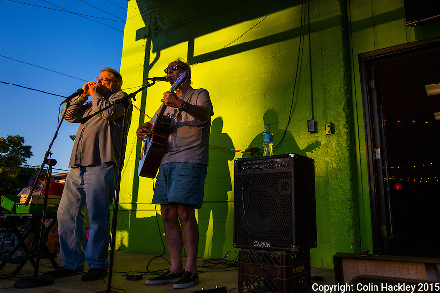 Mike Palecki on harmonica, left, and Ben Edmund   Powell on guitar anchor a corner venue during a first Friday performance at Tallahassee's Railroad Square.<br /> <br /> COLIN HACKLEY PHOTO