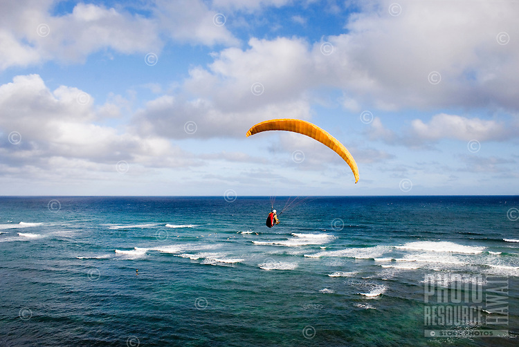 A paraglider soaring over the Pacific Ocean near O'ahu