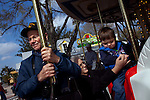 James Miller from New Oxford, Pennsylvania, left, sits beside Pat Carpenter, center, with Jay-Jay Disberry, 2, right, from Cirtrus County, Florida, as they ride on The Grand Carousel at the new theme park Legoland in Whitehaven, Florida on February 11, 2012.