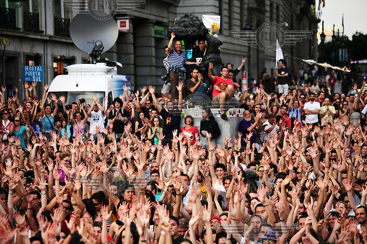 A large group of demonstrators raise their hands during a protest against cuts, austerity and joblessness in Madrid's Puerta del Sol square. In May 2012, following a worsening financial crisis and a deepening recession in Spain, thousands of people started to gather in Spanish cities to protest against austerity, the global financial system, high unemplyment rate (Spain's is the highest rate in Europe) and the lack of opportunities. The protest movement has become known as 'los indignados' (the indignant ones).