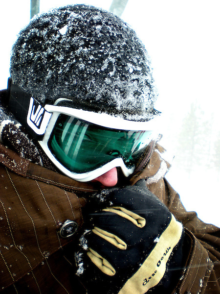 Portrait of a cold snowboarder covered in ice and snow. Lake Tahoe, California.