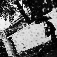 A pedestrian, holding an umbrella, walks on the street during a heavy rain in Quito, Ecuador, 30 October 2013.
