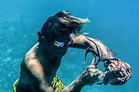 Marjono Lessing (35) grapples with an octopus he has just caught in the sea off Kabalutan. Octopus is one of the main sources of income for the Bajau.