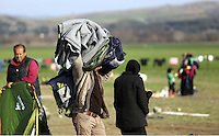 Pictured: A refugee man carries blankets and other belongings Thursday 25 February 2016<br /> Re: Refugees have been left stranded in temporary camps after Greek FYRO Macedonian borders were closed in Idomeni, northern Greece.