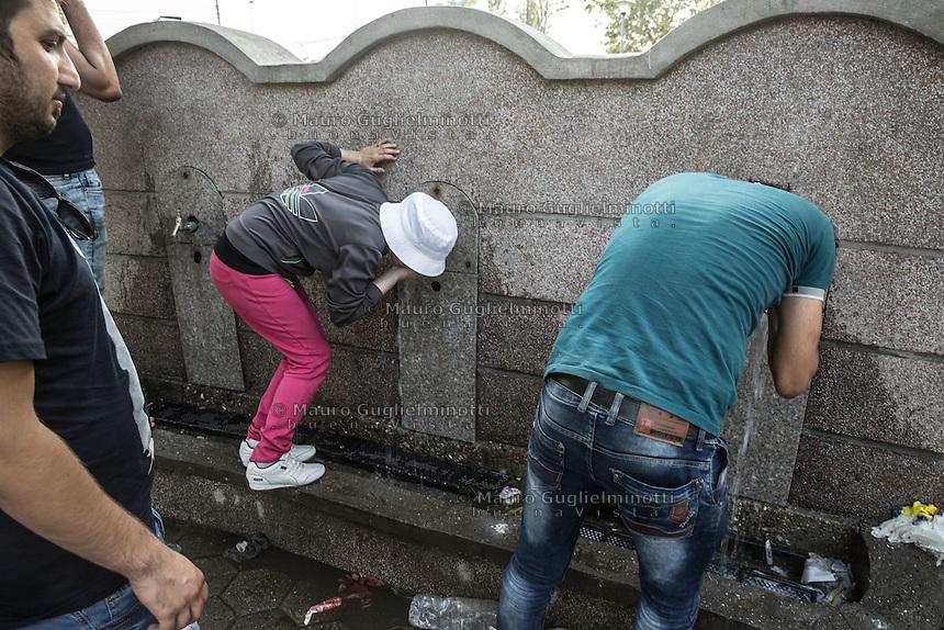 Migranti nel parco della stazione dei bus di Belgrado, bevono alla fontana. Migrants on the bus station park in Belgrade Beograd drinking at the fountain