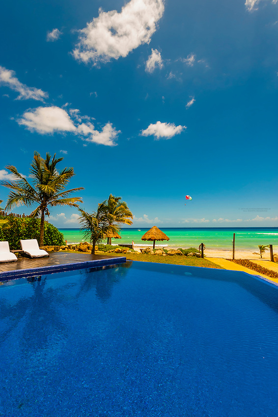 Infinity pool and palapas on a secluded beach with the Caribbean Sea in background, Le Reve Hotel, Riviera Maya, Quintana Roo, Mexico
