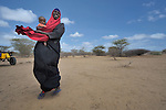 A woman holds her child as she pauses to rest while trekking across eastern Kenya. The woman left her home in Somalia a month earlier, fleeing drought and conflict, and heading to the Dadaab refugee complex. Already the world's world's largest refugee settlement, Dadaab has swelled in recent weeks with tens of thousands of recent arrivals from Somalia.