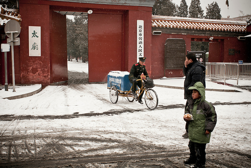 A member of the Armed police is transporting dustbin bags of the Work Ministry office (near the Forbidden city)  after a snowfall that local authorities say they have artifically provoked to fight the exceptional drought in northern China. February 10 2011