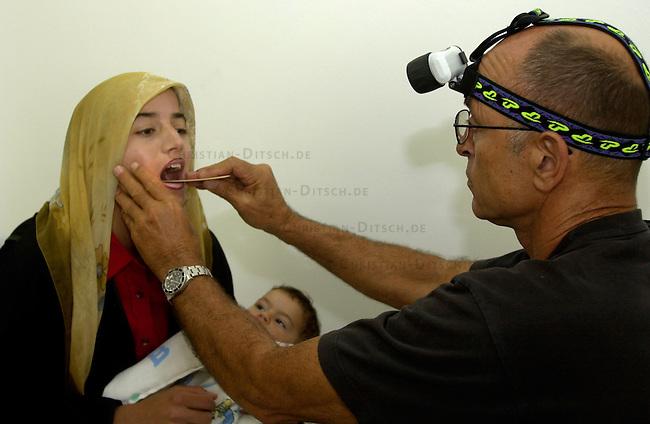 Medizinische Hilfe fuer Palaestinenser<br /> Seit Oktober 2000 ist die palaestinensische Stadt Bedia nahe Nablus nicht mehr von Israel per Auto zu erreichen. Von der israelischen Regierung aufgeschuettete Strassensperren sind fuer Fahrzeuge jeglicher Art unueberwindbar geworden. In der 10.000 Einwohnerstadt mangelt es an nahezu allem. Medizinische Versorgung gab es letztmals im Maerz diesen Jahres.<br /> Die rund 500 Mitglieder zaehlende israelisch-palaestinensische Menschenrechtsorganisation Physicians for Human Rights (PHR) hat nach einem Hilferuf des palaestinensischen Roten Kreuzes im Rathaus von Bedia eine medizinische Versorgung der Bevoelkerung durchgefuehrt (Medical Day). Rund 600 Personen konnten von 11 Aerzten und etlichen Krankenschwestern nach bis zu acht Stunden Wartezeit behandelt werden. Die Mediziner mussten an diesem Tag die dreifache Menge an Menschen versorgen. Die Patienten kamen zum Teil aus bis zu 35 km Entfernung. Das Gesundheitssytem in den palaestinensichen Autonomiegebieten ist nach Angaben der PHR seit dem Beginn der &quot;Operation Schutzschild&quot; kollabiert. Die meisten der erkrankten Kinder leiden an Atemwegs- und Viruserkrankungen.<br /> Die PHR existieren seit der ersten Intifada 1988 und haben sich zum Ziel gesetzt, in den palaestinensischen Gebieten ohne Ansehen der Herkunft und Zugehoerigkeit medizinische Hilfe zu leisten. Fuer schwer und chronisch Erkrankte versuchen die PHR-Mitarbeiter Transporte und klinische Versorgung in israelische und us-amerikanische Hospitaeler zu ermoeglichen. Bis auf zwoelf Hauptamtliche arbeiten alle anderen Mitglieder ehrenamtlich. Die Organisation finanziert sich durch Geld- und Sachspenden. Eine Zusammenarbeit mit israelischen Gesundheitsinstitutionen wird von Regierungsseite abgelehnt.<br /> Hier: Ein israelischer Arzt untersucht eine junge Mutter, die an einer schweren Kehlkopferkrankung leidet.<br /> Bedia / Israel, 18.05.2002<br /> Copyright: Christian-Ditsch.de<br /> [Inhaltsveraendernde Mani