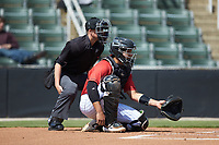 Kannapolis Intimidators catcher Jhoandro Alfaro (32) sets a target as home plate umpire Jose Lozada looks on during the game against the Lexington Legends at Kannapolis Intimidators Stadium on May 15, 2019 in Kannapolis, North Carolina. The Legends defeated the Intimidators 4-2. (Brian Westerholt/Four Seam Images)