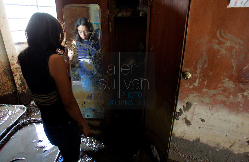 Carolina de Rosales checks on the soiled contents of her family's home, damaged by mudslides about two weeks prior. In early October a nearby river sent torrents of water and mud through the town, which sits near Antigua, and destroyed several homes after rains associated with Hurricane Stan inundated parts of Central America. Torrential rains and mudslides killed or made missing thousands of Guatemalans in early October.<br />