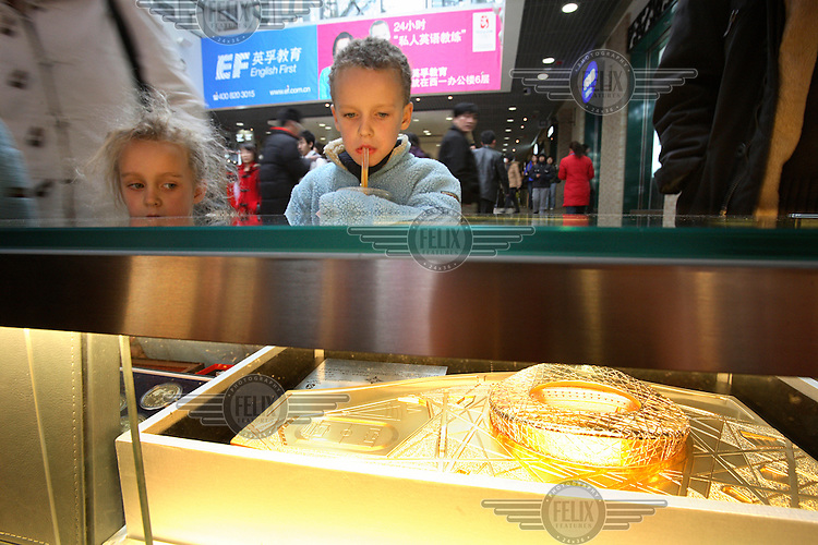 "Western children looking at a gold plated replica of the famous ""Bird's Nest"" Olympic stadium, at the Olympic gift shop in central Beijing."