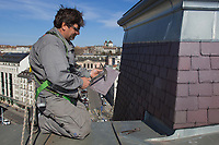 Switzerland. Geneva. A laborer from the company Cerutti Toitures SA is working on a roof in the town center. View on the old town and the St. Pierre Cathedral. The St. Pierre Cathedral is a cathedral which belongs to the Reformed Protestant Church of Geneva.19.03.2014 © 2014 Didier Ruef