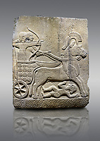 Picture &amp; image of Hittite relief sculpted orthostat stone panel of Long Wall Basalt, Karkamıs, (Kargamıs), Carchemish (Karkemish), 900 - 700 B.C.  Anatolian Civilizations Museum, Ankara, Turkey<br /> <br /> Chariot. One of the two figures in the chariot holds the horse's headstall while the other throws arrows. There is a naked enemy with an arrow in his hip lying face down under the horse's feet. It is thought that this figure is depicted smaller than the other figures since it is an enemy soldier. The tower part of the orthostat is decorated with braiding motifs.<br /> <br /> On a gray background.