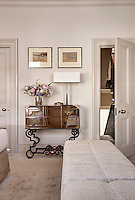 A table lamp and a flower arrangement stands on an ornate mirrored console table in a bedroom decorated in neutral tones.