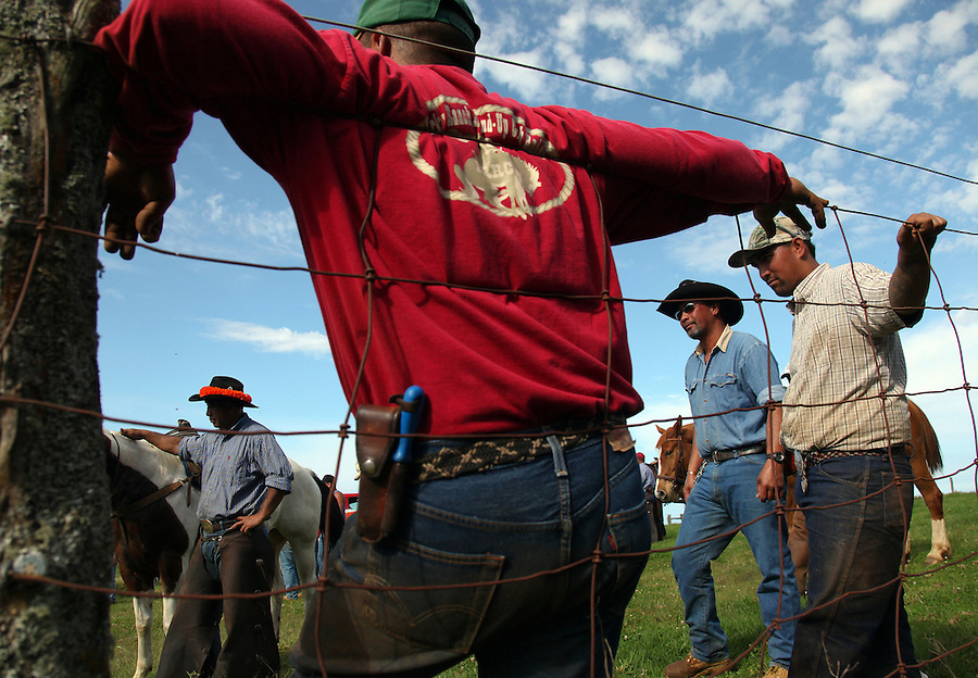 "Cowboys from different ranches take a break from the work of branding, innoculating, tagging and in the case of males, castrating calves at Ponoholo Ranch in North Kohala, Hawaii. Indispensable to the cowboys are their knives which they carry on their belts.  ""Sometimes you have to cut yourself free of a rope to prevent yourself being pulled off your horse or getting an arm or leg caught,"" says Wayne Tachera who himself lost a finger in a roping accident."