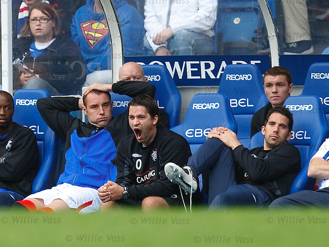 Kris Boyd taking it esy on the bench as fitness coach Adam Owen yawns