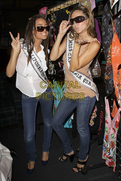 MISS TEEN CALIFORNIA CHELSEA GILLIGAN & MISS CALIFORNIA TAMI FARRELL.Visiting Ed Hardy Headquarters,  Ed Hardy Outlet, Culver City, California, USA, 25th September 2009..full length jeans sash beige vest top white blouse sleeveless sunglasses v peace sign .CAP/ADM/KB.©Kevan Brooks/AdMedia/Capital Pictures.