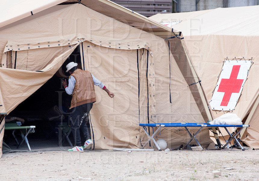 Migranti nella tendopoli allestita presso la stazione Tiburtina a Roma, 16 giugno 2015.<br /> A migrant enters a tent in the camp set up near the Tiburtina railway station in Rome, 15 June 2015. Italy is facing a huge flow of migrants brought to Sicily after rescue at sea, many of whom are trying to join their relatives in northern Europe. <br /> UPDATE IMAGES PRESS/Riccardo De Luca