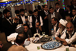 Hundreds of family members and friends - carefully divided between side's for men and women - attend a wedding at the lavish Mumtaz Majal wedding hall in Kabul. Glistening wedding halls dot the Kabul city scape and their attendance - which always includes large dinners and energetic dancing - is a mainstay of Kabuli social life. Here men from both sides of the family as well as elders and religious leaders come together to agree on the bride price and solemnize the wedding with verses from the Q'uran. The groom, speaking to his mullah whose back is towards the viewer, is seated center-left. The negotiated bride price was $15,000 - a princely sum to most in impoverished Afghanistan. Summer 2010.