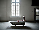 woman sitting in a bath with bunny mask in a abandoned hospital