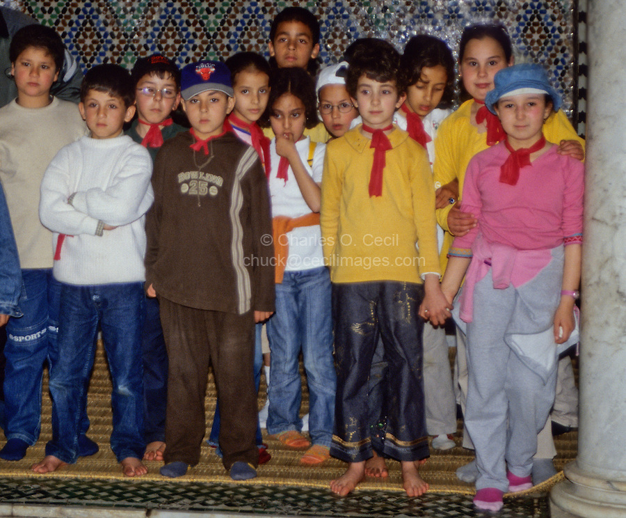 Meknes, Morocco.  School Children Visiting the Mausoleum of Moulay Ismail.  They have removed their shoes because they are in a mosque.