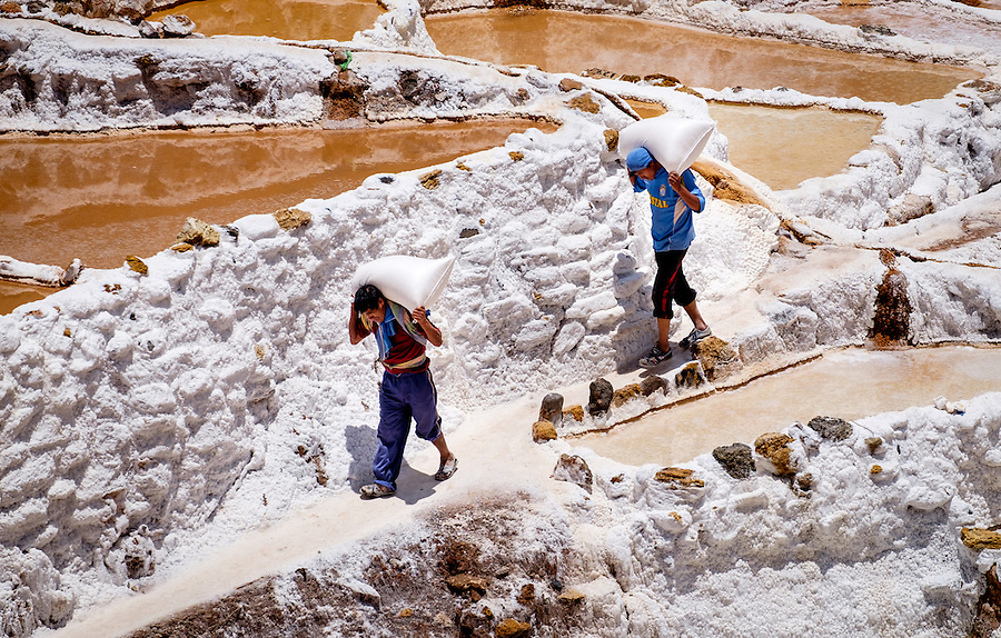 MARAS, PERU - CIRCA OCTOBER 2015:  Workers carrying bags at the Marasal salt plains near the village of Maras in the Cusco region known as Sacred Valley
