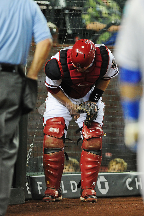 May 21, 2012; Phoenix, AZ, USA; Arizona Diamondbacks catcher Miguel Montero reacts and grabs his thigh after suffering an injury chasing down a foul ball against the Los Angeles Dodgers in the sixth inning at Chase Field.  Mandatory Credit: Mark J. Rebilas-