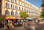 People sitting outside popular cafes on a sunny afternoon in Plaza de la Merced, Malaga, Spain