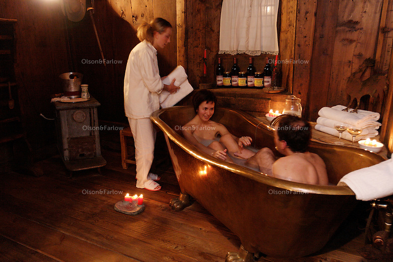 Rural charm attracts spa goers who pay for champagne with their milk and honey bath and relax in a bed of straw for a rustic experience in Cogne, Italy<br /> Silvia, Rodolfo Borney take a milk and honey bath, one of several luxury spa treatments. They are served champagne and then relax in a bed of straw with more champagne..