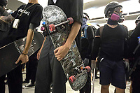 CHINA, Hong Kong: 21 August 2019 <br /> Young protesters with their skateboards watch on as others clash with riot police inside Yuen Long Station after the train station was filled with protesters angry about the Yuen Long attack which happened exactly one month ago.  <br /> The attack, on 21st of July, was by approximately 100 men who violently attacked protesters, reporters and a pregnant woman. No arrests were made and it is believed the gang were colluding with the police.<br /> Rick Findler / Story Picture Agency