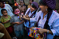 'Twin Teachers' Rian and Rossy distributing milk biscuits to the children in a remote village in Indonesia's Papua province where they have one of their schools. Since the early 1990s, twin sisters Sri Rosyati (known as Rossy) and Sri Irianingsih (known as Rian) have used their family inheritance to set up and run 64 schools in different parts of Indonesia, providing primary education combined with practical skills to some of the country's most deprived children.