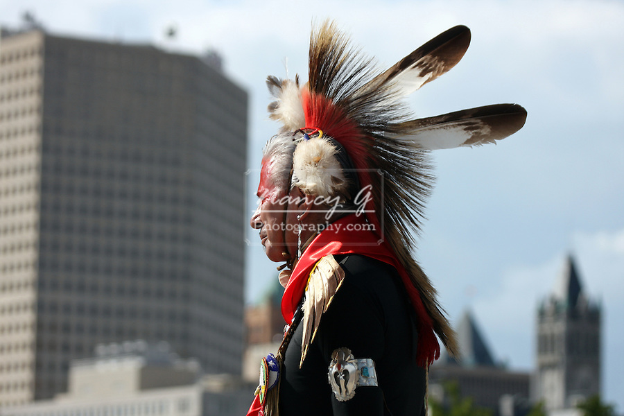 A Native American Indian man standing infront of the buildings at the lake front of Lake Michigan, Milwaukee Wisconsin