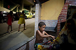 A boy plays video games in the community of Babylonia, in Rio de Janeiro, Brazil, on May 19, 2013. Babylonia and neighboring Chapeu Manguiera, above Leme and Copacabana neighborhoods, were once rival favelas with enemy drug gangs but after pacification this small community is no longer experiences violence.