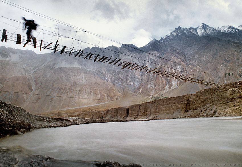 A backpacker crossing a suspended bridge over the Hunza river in Gojal region, near Hunza, Northern Pakistan.