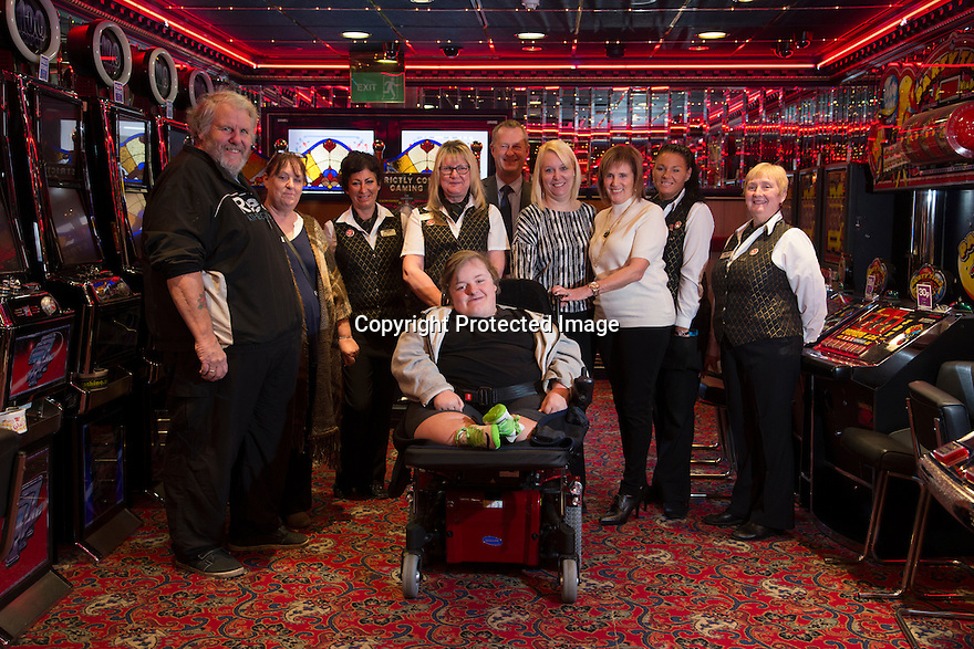 """20/11/15<br /> <br /> L/R: Alan Kent, Diane Kent, Lorna Cord, Helen Stockdale, Arron Kent, Simon Gudgeon, Wanda Kidd, Linda Lindsay, Gemma Wylie and Janet Neal.<br /> <br /> Thanks to the joint fundraising efforts of customers and staff at Cashino adult gaming centre on Station Street Burton-On-Trent, Arron Kent, a seventeen year old teenager from Swadlincote has received a new, customised powered wheelchair to help boost his mobility. <br /> <br /> Arron, who lives with his mum, Diane, dad Alan and sister Tabitha, suffers from Osteogenesis Imperfecta – a severe brittle bone disease which has seriously affected Arron's ability to walk. His condition means his bones break easily, often from mild trauma or with no apparent cause.  <br /> <br /> Arron currently has a basic powered wheelchair  but as his condition progresses the chair is becoming inadequate to meet Arron's growing needs. <br /> <br /> Arron's mum Diane said: """"We are very grateful to Cashino and CHIPS charity for providing Arron with a new state of art powered wheelchair. As he develops into adulthood, it is important that he maintains his independence, this powered wheelchair with features including adjustable height, tilt in space and excellent manoeuvrability will literally revolutionise Arron's life. <br /> <br /> Diane continues """"Arron is developing his hobby of showing rabbits and the rise and fall feature of his new wheelchair means he can now reach the judging tables without needing the assistance of another person.""""<br /> <br /> Cashino, which operates 155 adult gaming centres across the country, is one of the main fundraisers for CHIPS, a charity set up on behalf of the casino and gaming industry, which aims to provide specialised wheelchairs for children and young people with severe mobility problems.<br /> <br /> Janet Neal, manager of Cashino Burton-On-Trent, presented Arron with his new wheelchair last Friday, 20th November 2015.<br /> <br /> Speaking after the presentation, Janet Neal said"""